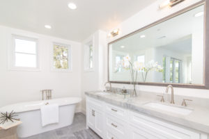 white bath tub, marble bathroom counters, double sink bathroom